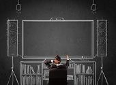 stock photo of home theater  - Young businessman sitting and enjoying home cinema system sketched on a chalkboard - JPG