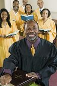 stock photo of preacher  - Portrait of happy preacher with Holy Bible while choir standing in background at church - JPG