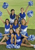 stock photo of cheerleader  - Portrait of beautiful cheerleaders holding pompoms on field - JPG