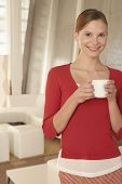 Portrait of confident young businesswoman holding coffee cup in office lobby