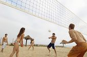 Group of multiethnic friends playing volleyball on beach