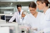 stock photo of centrifuge  - Male technicians discussing in lab with female colleagues working in foreground - JPG