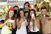 Group of happy German soccer fans holding smartphones.