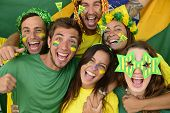 stock photo of enthusiastic  - Happy group of Brazilian sport soccer fans amazed celebrating victory together - JPG