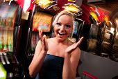 stock photo of gambler  - Young woman in Casino on a slot machine - JPG