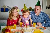 Family of three sits at birthday table, daughter snuffes out candle on cake and parents look at her