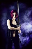 stock photo of swords  - Beautiful girl warrior with a sword standing in fighting stance - JPG