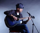 stock photo of pop star  - Young musician playing acoustic guitar and singing - JPG
