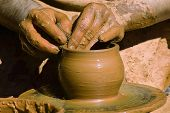 stock photo of molding clay  - Potter hands making in clay on pottery wheel - JPG