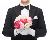 wedding, anniversary, special occasion concept - close up of man in tail-coat with bouquet of roses