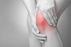 image of knee  - A young woman massaging her painful knee - JPG