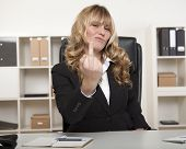 pic of obscene gesture  - Pretty young blond businesswoman making a rude gesture with her middle finger at the camera as she pulls a face showing her disgust - JPG