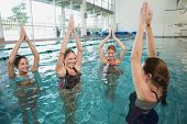 stock photo of day care center  - Smiling female fitness class doing aqua aerobics in swimming pool at the leisure centre - JPG