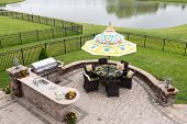 picture of angle  - Outdoor living space on a brick patio overlooking a tranquil lake and fenced green lawn with a table under a sunshade or umbrella laid ready for dinner high angle view - JPG