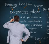 stock photo of half-dressed  - Thinking businessman against blue chalkboard with business buzzwords - JPG