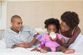 picture of babygro  - Happy parents with baby girl on their bed at home in the bedroom - JPG