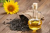 stock photo of sunflower-seeds  - sunflower oil seed and sunflower on the background of wooden boards - JPG