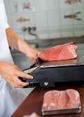 foto of slaughterhouse  - Cropped image of male butcher weighing meat on weight scale in shop - JPG