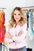 stock photo of racks  - Beautiful young stylist near rack with hangers - JPG