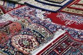 stock photo of iranian  - many colourful Oriental rugs for sale in the shop of rugs - JPG