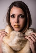 pic of snuggle  - Attractive young woman wearing furry winter fashion snuggling down into the softness and warmth of the fur while looking at the camera with parted lips - JPG