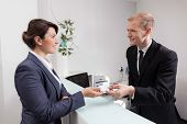 stock photo of receptionist  - Young handsome receptionist giving woman the key to her room  - JPG