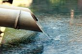stock photo of peace-pipe  - water falling down from yellowe bamboo pipe - JPG