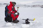 pic of ice fishing  - Man ice fishing on a cold winter day - JPG