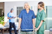stock photo of nursing  - Female nurse assisting senior woman to walk with Zimmer frame at nursing home - JPG