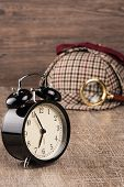 stock photo of private investigator  - Deerstalker or Sherlock Hat and magnifying glass on Old Wooden table - JPG