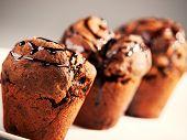 stock photo of chocolate muffin  - Three chocolate muffins shot over gray background - JPG