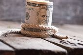 stock photo of fifties  - American Fifty Dollar Bills rolled up and rope on a wooden table - JPG