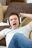 pic of singing  - Man singing listening to music over headphones enjoying relaxing on sofa - JPG