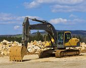 stock photo of excavator  - Yellow excavator on a construction site against blue sky - JPG