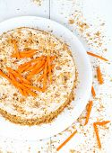 stock photo of carrot  - Gourmet homemade carrot sponge cake with carrot slices and walnut crumbs on white background - JPG