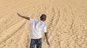 stock photo of ten  - Afro boy walking in the sand - JPG