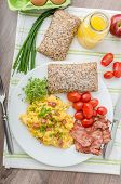 foto of scrambled eggs  - Scrambled eggs with bacon chive and tomatoes fresh juice and little microgreens healthy salad - JPG