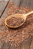 stock photo of flax plant  - Healthy little brown flax seeds super foods  in wooden spoon - JPG