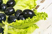 picture of olive shaped  - Black olives in a green salad leaf - JPG