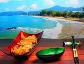 image of deep  - traditional Vietnam deep fried shrimp and pork rolls in breadcrumbs served on a wood table top by the beach - JPG