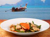 pic of stir fry  - chicken stir fry thai style on a wood table beside the beach - JPG