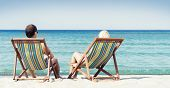 picture of couple sitting beach  - Young couple sitting in a beach chairs and looking at the sea - JPG