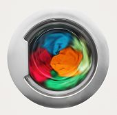 foto of dirty-laundry  - Washing machine door with rotating garments inside - JPG