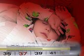 foto of high fever  - Mercury thermometer showing high temperature and a little sick girl in bed - JPG