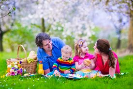 stock photo of eat grass  - Young family with kids having picnic outdoors - JPG