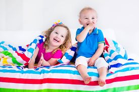 foto of little sister  - Two kids sleeping in bed under colorful blanket - JPG