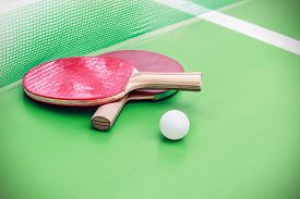 image of ping pong  - table tennis or ping pong rackets and balls on a green table with net - JPG