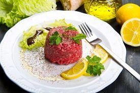 foto of tartar  - Close up of beef tartar with fresh salad and lemon slice - JPG