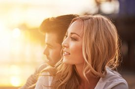 picture of cuddle  - romantic couple cuddling on beach at sunset with lens flare - JPG