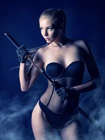 stock photo of sword  - Sexy blonde in lingerie on black background manipulates Japanese sword with sexual overtones - JPG